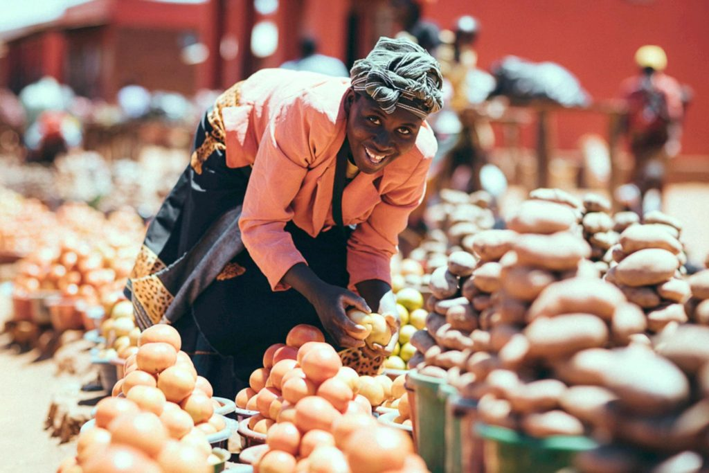Woman smiling over her produce in the market