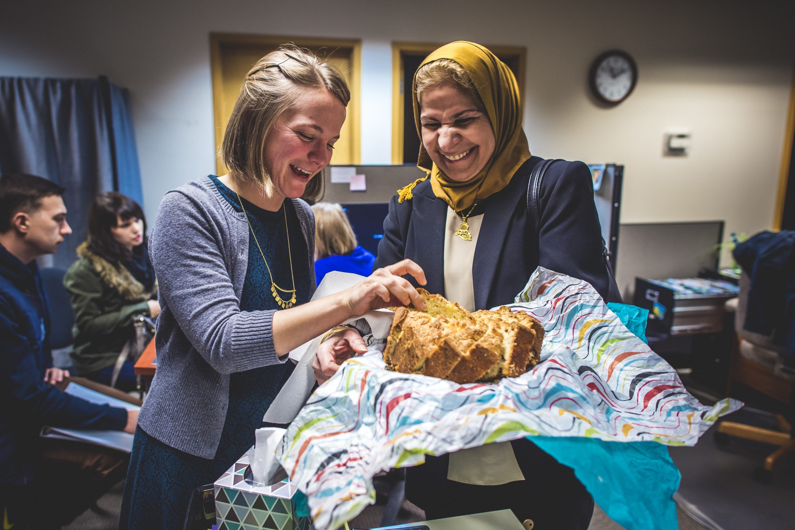 Two women smiling and laughing with baked bread