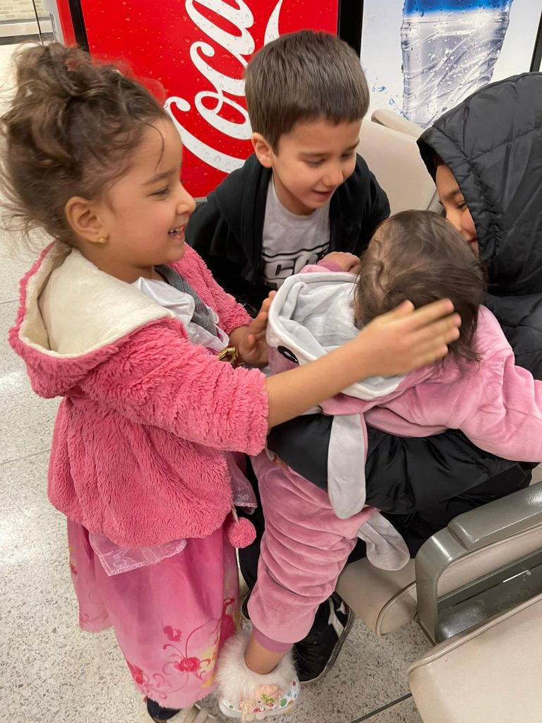 A refugee child is hugged by her siblings when she arrives at the Memphis airport.