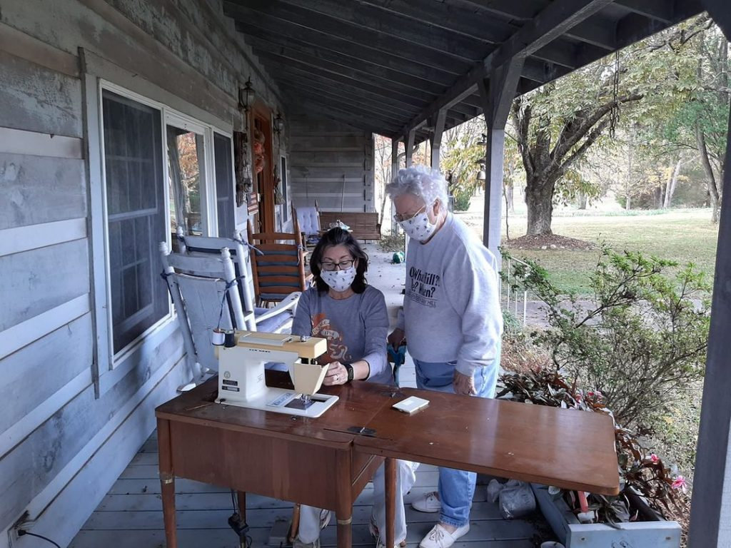 Melissa sews with her grandmother outside following COVID protocols.