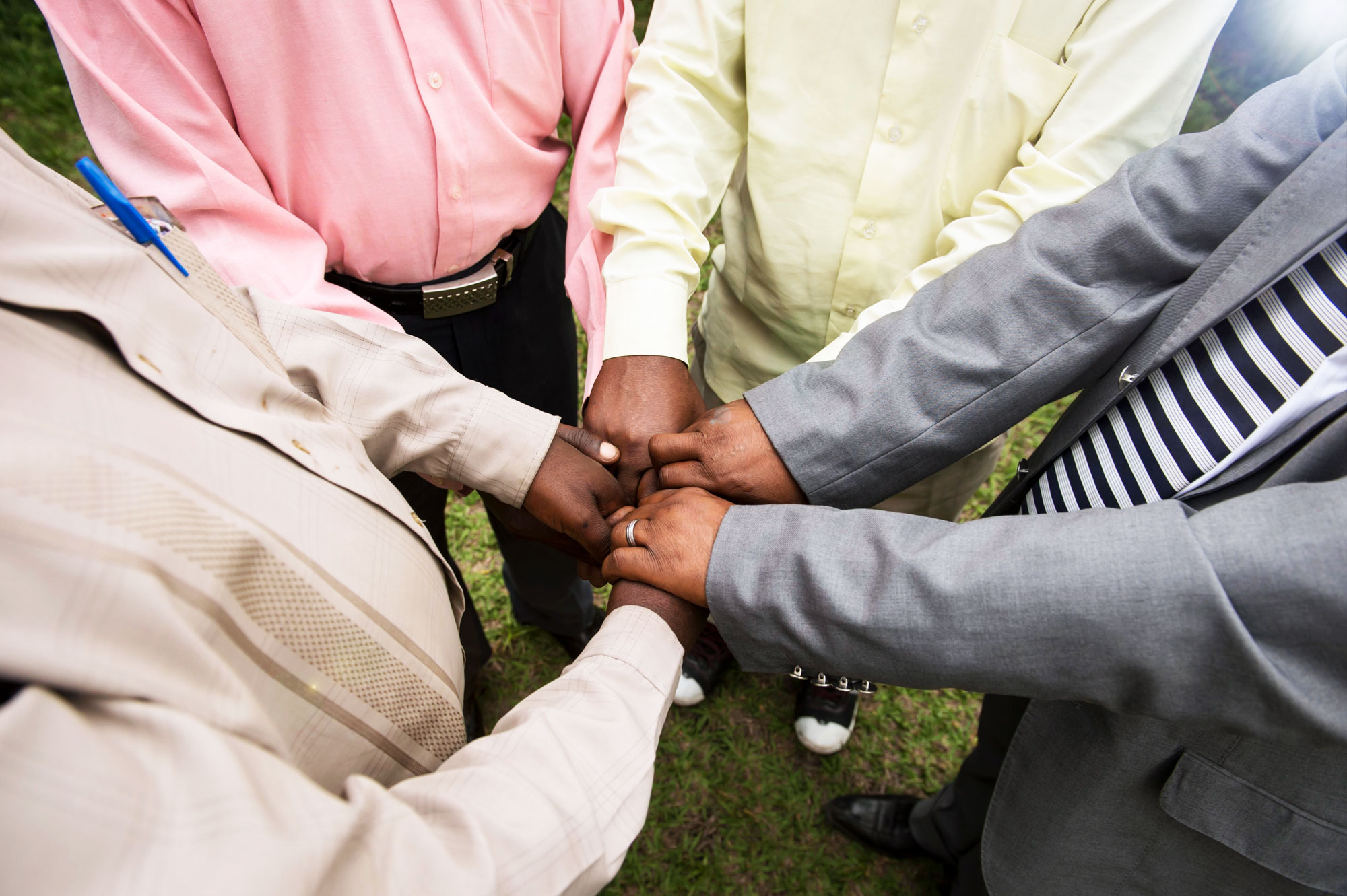 Group of people with hands in the middle in fists